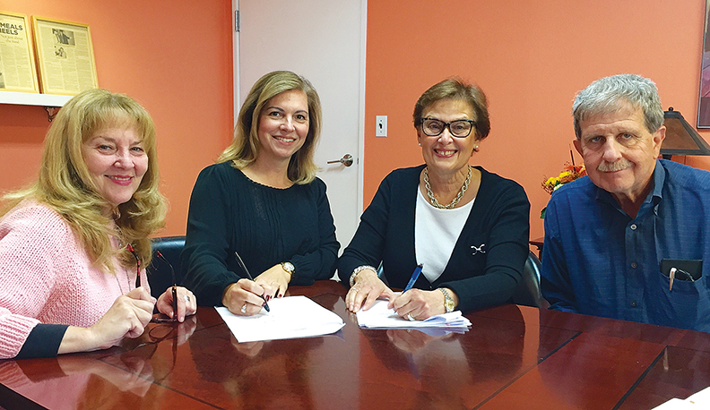 Susan Greenbaum looks on as JFS presidents Shira Feuerstein, center, and Allyn Michaelson sign the agreement to join their two agencies to create the Jewish Family and Children's Services of Northern New Jersey.