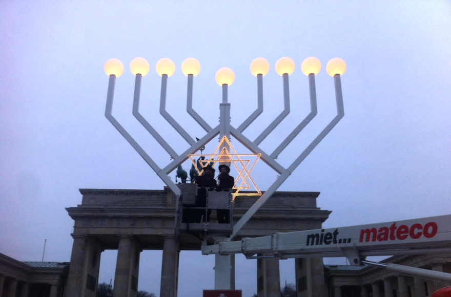 Rabbi Yehudah Teichtal, left, and a colleague testing out a Hanukkah menorah at the Brandenburg Gate in Berlin, December 22, 2016. (Courtesy of Teichtal/via JTA)
