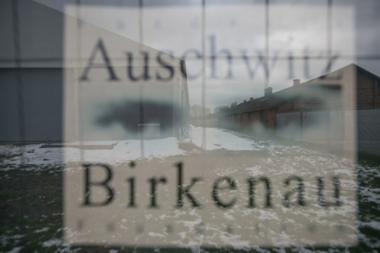 Barracks are seen through a poster at the former Nazi concentration camp in Oswiecim (Auschwitz), Poland, on December 2, 2016. (AFP PHOTO / BARTOSZ SIEDLIK)