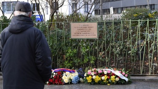 A man stand in front of a memorial plaque for Ahmed Merabet, one of the victims of f the deadly attack against the satirical weekly Charlie Hebdo during the ceremony marking the second anniversary of the attack, on January 5, 2017 in Paris. (AFP PHOTO / Eric FEFERBERG)
