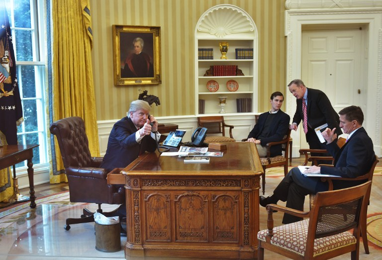 US President Donald Trump(L)seen through an Oval Office window gives a thumbs up as he speaks on the phone to King Salman of Saudi Arabia in the Oval Office of the White House on January 29, 2017 in Washington, DC. (AFP PHOTO / MANDEL NGAN)