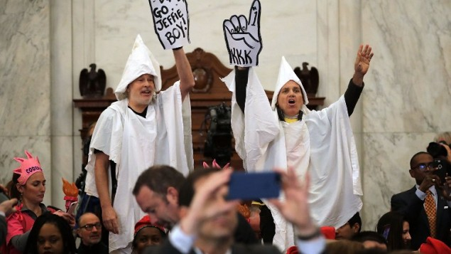 Protesters wearing white sheets shout at Sen. Jeff Sessions (R-AL) as he arrives for his confirmation hearing to be the US attorney general on 10, 2017 in Washington, DC. (Somodevilla/Getty Images/AFP)