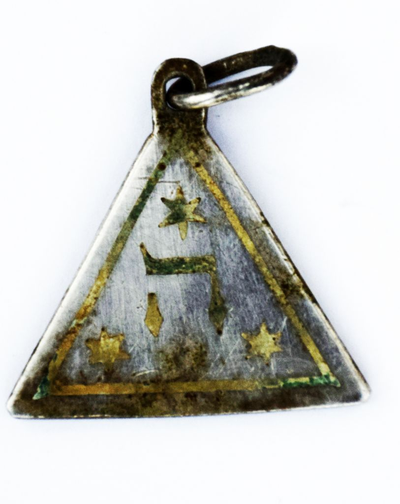 The reverse of a pendant showing the Hebrew letter symbolizing God's name found at the site of the Nazi-operated Sobibor death camp