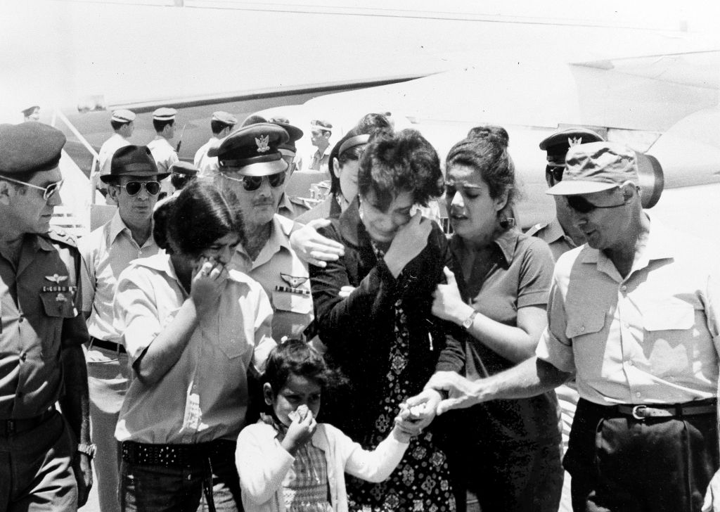 Israeli Defense Minister Moshe Dayan, (r), comforts the family of Israeli Col. Yosef Alon after the family arrived at Lod Airport in Israel with Alon's body, July 2, 1973. (AP Photo/stf)