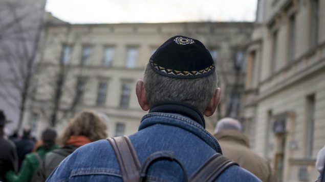 A kippah-clad man man taking part in a silent march in Berlin to commemorate the 75th anniversary of the Kristallnacht pogroms, Nov. 9, 2013. JTA
