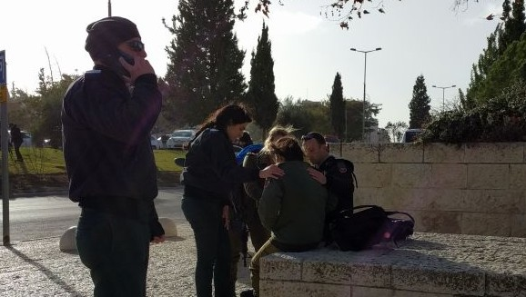 "Social workers with the army utilize the ""bilateral stimulation"" trauma response method to help calm a witness by applying physical pressure on both sides of their body, after the truck ramming attack on January 8, 2017. (Melanie Lidman/Times of Israel)"