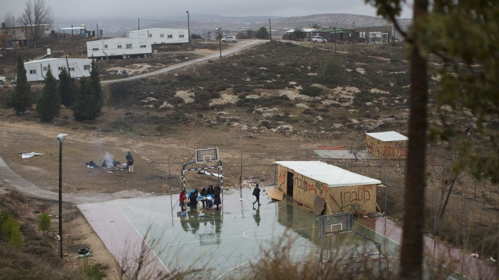 In this Sunday, December 18, 2016 file photo, Jewish settlers cook food on a basketball court in Amona, an unauthorized Israeli outpost in the West Bank, east of Ramallah. (AP Photo/Oded Balilty, File)