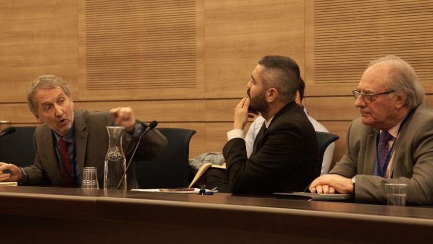 David Horovitz, editor of The Times of Israel (left), speaks to the Knesset State Control Committee session on binary options fraud, January 2, 2017. At right is English binary options victim Graham Towler, who also addressed the session. (Luke Tress / Times of Israel)