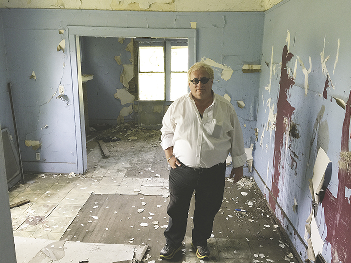 Tuvia Tenenbom stands in a devastated room in a devastated building in Detroit.