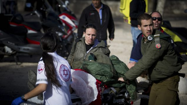 Medics attending to the injured at the scene where a truck rammed a group of Israeli soldiers in eastern Jerusalem, Jan. 8, 2017. (Yonatan Sindel/Flash90)