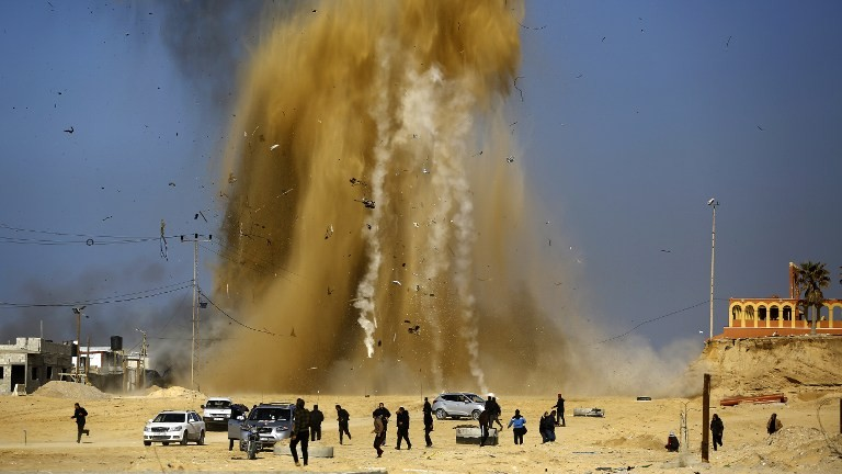 Palestinians run for cover as sand and smoke rise following an Israeli airstrike on a Hamas post in the northern Gaza Strip on February 6, 2017. (Mohammed Abed/AFP)