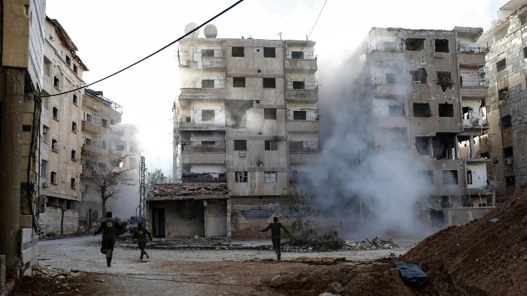Syrian civil defense volunteers run amid the smoke as they search for survivors following a reported government airstrike on the rebel-held town of Douma outside Damascus