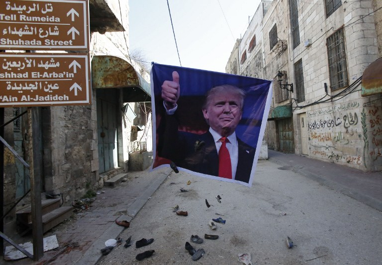 A general view shows old shoes being thrown by Palestinian demonstrator at a poster of US President Donald Trump as they protest against his support of Israel and demand for the Israeli army to re-open Shuhada Street near a Jewish settler enclave in the heart of the flashpoint West Bank city of Hebron, which it has largely closed off to Palestinians on February 24, 2017. (AFP PHOTO / HAZEM BADER)