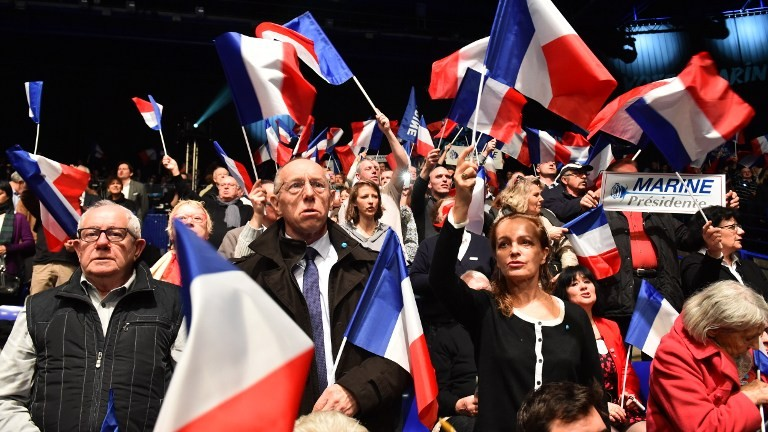Supporters of the French far-right National Front (FN) party wave French flags during a campaign rally of the party's candidate for the presidential election, on February 26, 2017 at the Zenith de Nantes venue in Saint-Herblain. (AFP Photo/Jean-Francois Monier)