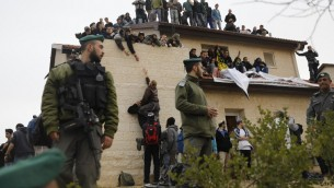 Israeli security forces stand guard as right-wing activists take positions on the rooftop of a home slated for demolition during an operation to clear out nine houses in the Jewish settlement of Ofra, in the West Bank, on February 28, 2017. (Menahem Kahana/AFP Photo)