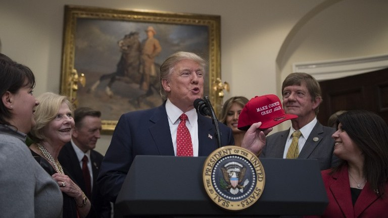"US President Donald Trump (C) holds up a red cap that reads ""Make Counties Great Again"" before signing the Waters of the US (WOTUS) executive order at the White House on February 28, 2017. (AFP Photo/Jim Watson)"