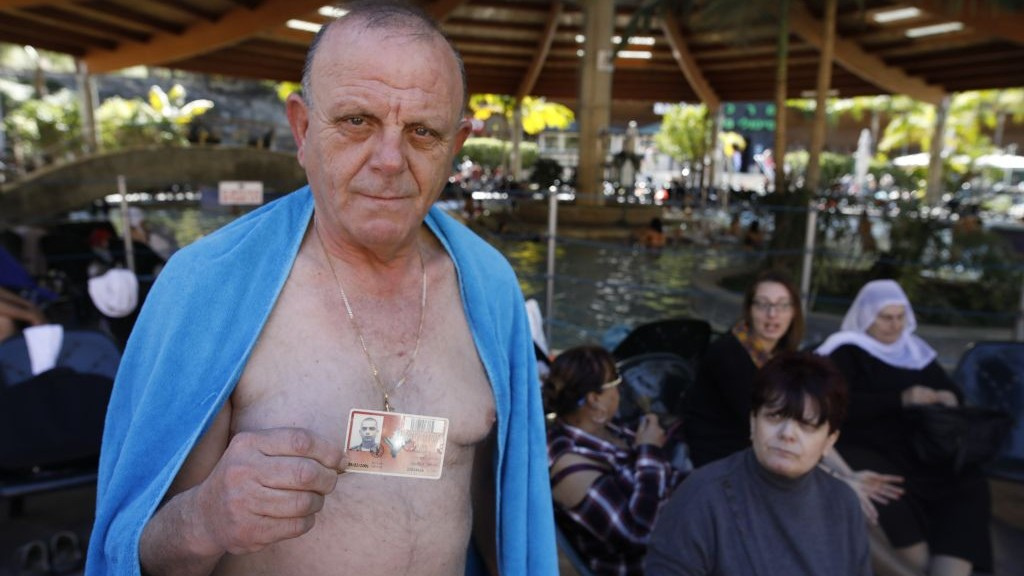 After bathing in the hot springs of Hamat Gader, Israel on February 20, 2017, Jawdat Salame shows the military ID of his son Rojiya, who was killed on was killed by Palestinian sniper near Rafah, in the Gaza Strip in 2001. His wife Nadra is sitting beside him. (Courtesy)