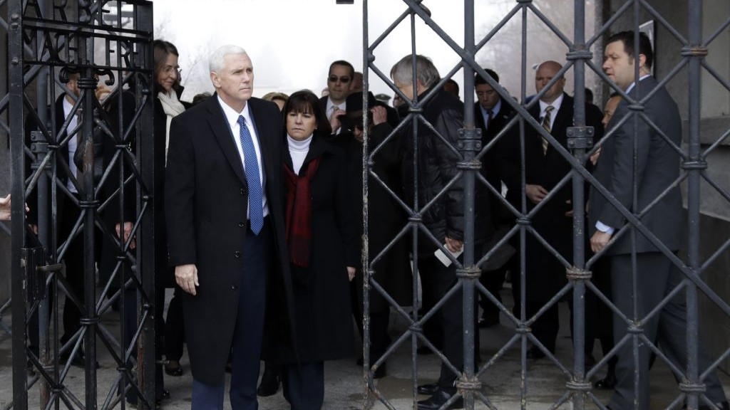 """US Vice President Mike Pence and his wife Karen go through the gate with the writing """"Works sets you free"""" as they a visit the former Nazi concentration camp in Dachau near Munich, Germany, Sunday, Feb. 19, 2017. (AP Photo/Matthias Schrader)"""