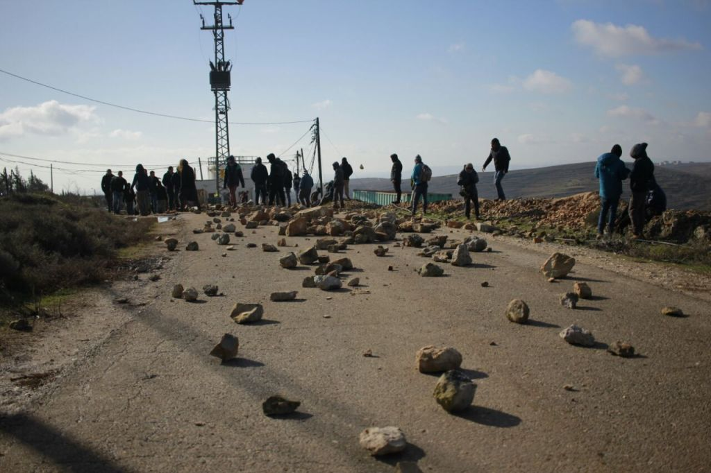 Israeli protesters place boulders on the road leading into the illegal West Bank outpost of Amona ahead of its demolition, on February 1, 2017. (Judah Ari Gross/Times of Israel staff)