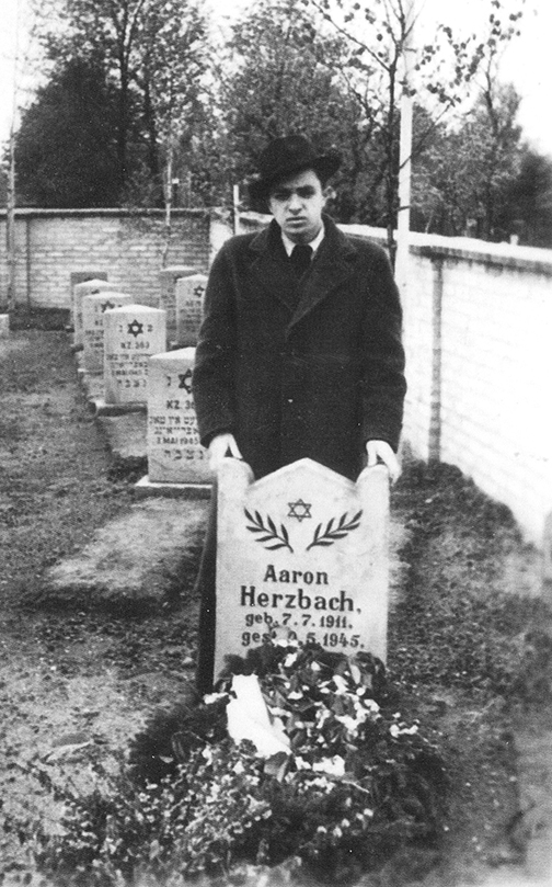 Hirsch stands at his cousin's grave in Neustadt-Holstein, Germany. The two survived the camps together, but Aaron died the week after he was liberated.