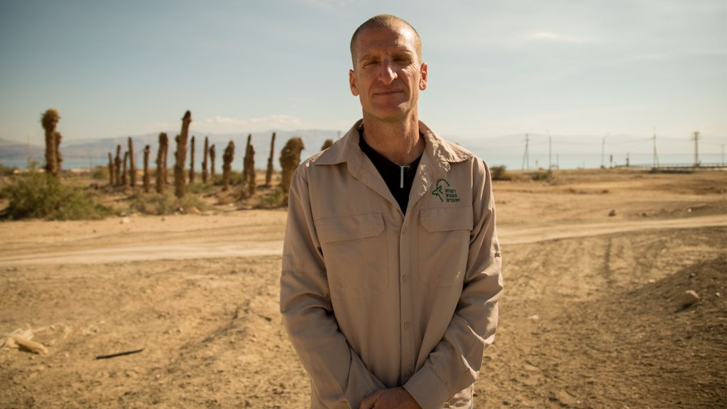 Harel Ben Shahar, the director of the Arava Region for Nature and Park's Authority, which includes the Ein Gedi reserve, stands in front of an abandoned date orchard near the nature reserve on January 3, 2017. (Luke Tress/Times of Israel)