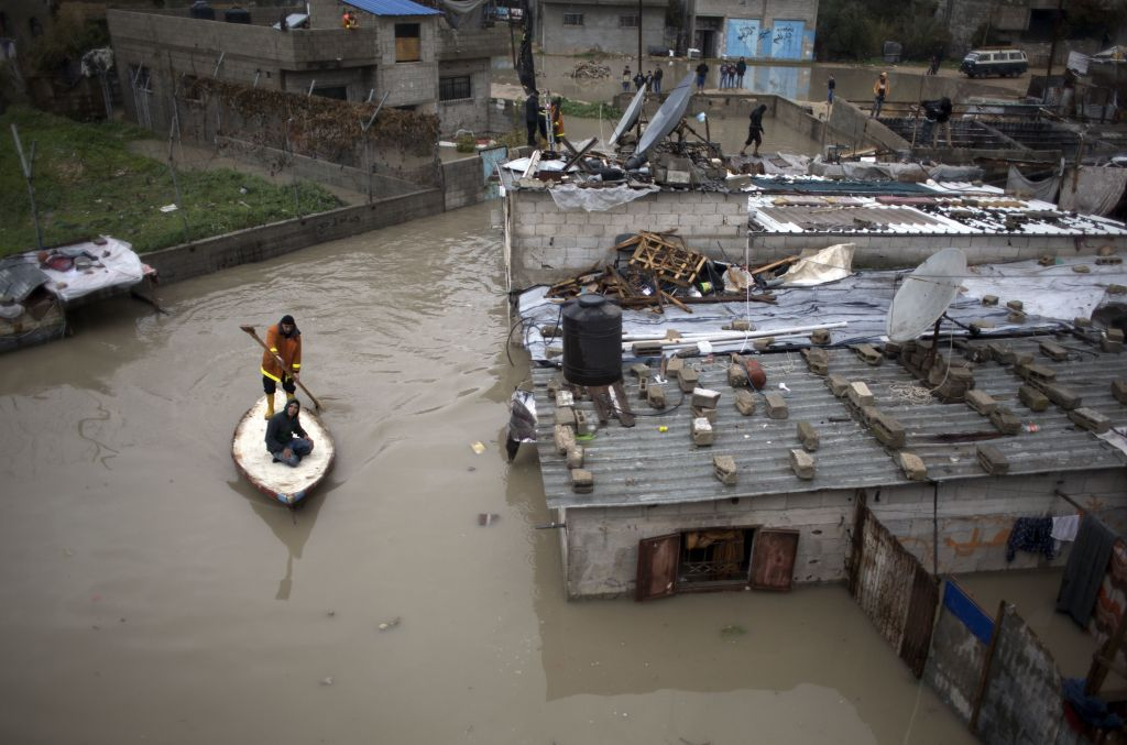 Palestinian rescuers members evacuate a man from a flooded home using a fishing boat during a heavy rain storm in Jabaliya refugee camp, northern Gaza Strip, Thursday, Feb. 16, 2017 (AP Photo/ Khalil Hamra)