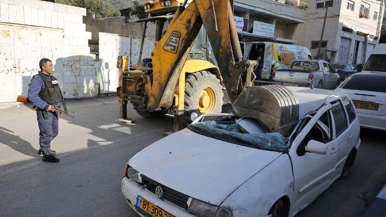 A bulldozer smashes its shovel into a car with an Israeli license plate in the West Bank village of al-Ram on March 6, 2017. (AFP Photo/Abbas Momani)