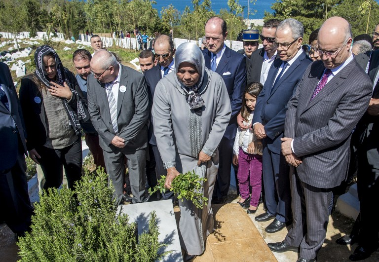 Latifa Ibn Ziaten (C), president of the French IMAD association and mother of French soldier Imad Ibn Ziaten, who was killed by Islamist gunman Mohamed Merah on March 8, 2012, places laurels upon a grave during a ceremony commemorating her son in a cemetery in the Moroccan city of M'diq on March 11, 2017, where she is accompanied by French ambassador in Rabat Jean-François Girault (C-R). (AFP PHOTO / FADEL SENNA)