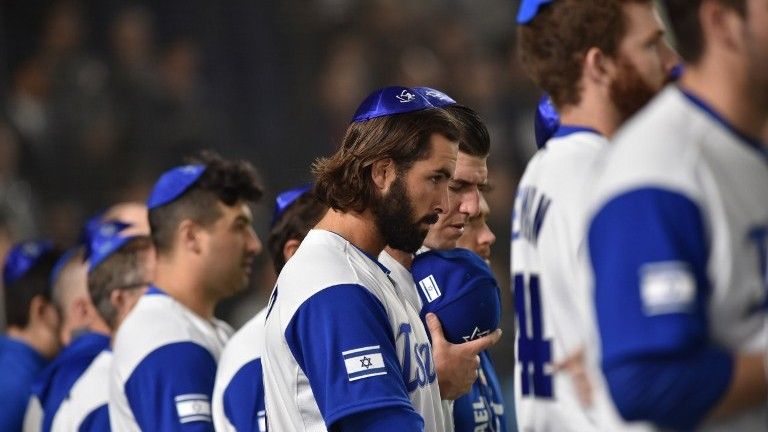 Israel's pitcher Joey Wagman (C) and his teammates sing the national anthem prior to the team's second round match against The Netherlands in Tokyo on March 13, 2017. (AFP Photo/Kazuhiro Nogi)