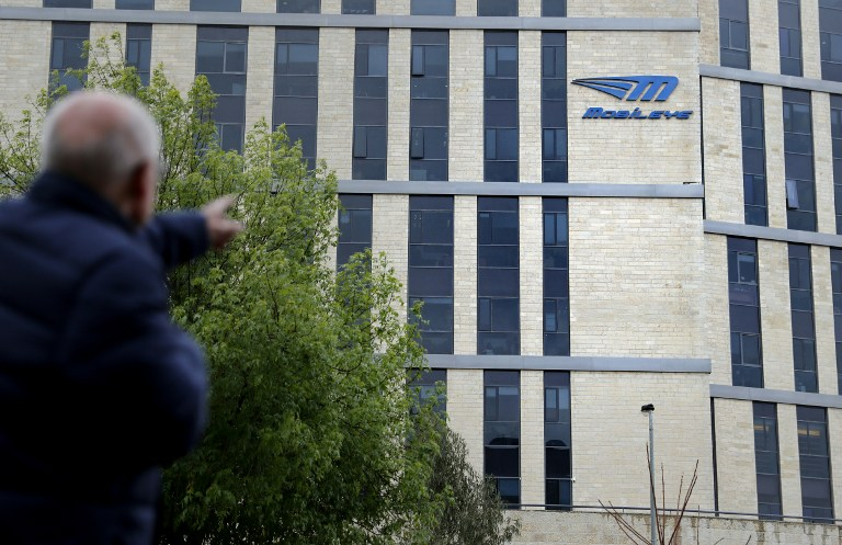 A man walks past the logo of Israeli car tech firm Mobileye on the company's offices in Jerusalem on March 13, 2017. Intel will buy Mobileye for more than $15 billion (14 billion euros), the companies said on March 13, 2017, in a deal signalling the US computer chip giant's commitment to technology for self-driving vehicles. (AFP PHOTO / THOMAS COEX)