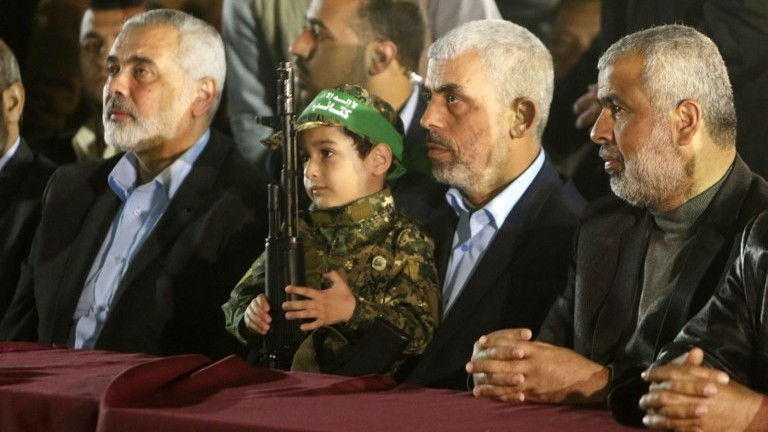 Hamas's new leader in the Gaza Strip Yahya Sinwar (2nd R) and senior political leader Ismail Haniyeh (L) sit next to the son of assassinated Hamas terrorist Mazen Faqha on March 27, 2017, in Gaza City. (AFP Photo/Mahmud Hams)