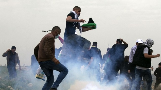 Palestinian demonstrators run as Israeli security forces fire tear gas toward them following a protest to mark Land Day in the village of Madama, south of Nablus, in the West Bank, March 30, 2017. (AFP/JAAFAR ASHTIYEH)