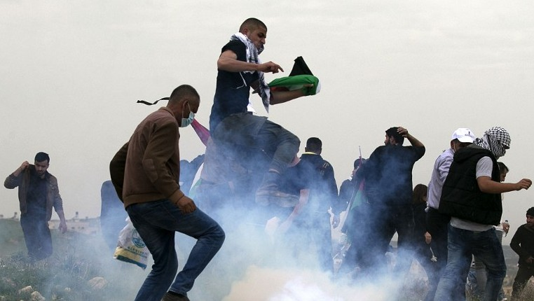 Palestinian demonstrators run as Israeli security forces fire tear gas toward them following a protest to mark Land Day in the village of Madama south of Nablus in the West Bank