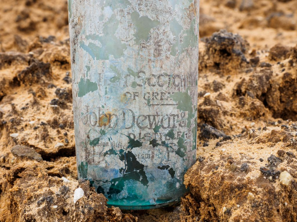A bottle of Dewar's whisky with the label found at a World War I British camp near Ramle in March 2017 (Assaf Peretz, courtesy of Israel Antiquities Authority)