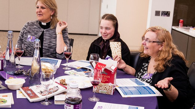 Christian and Jewish guests opening their box of matzah at the seder