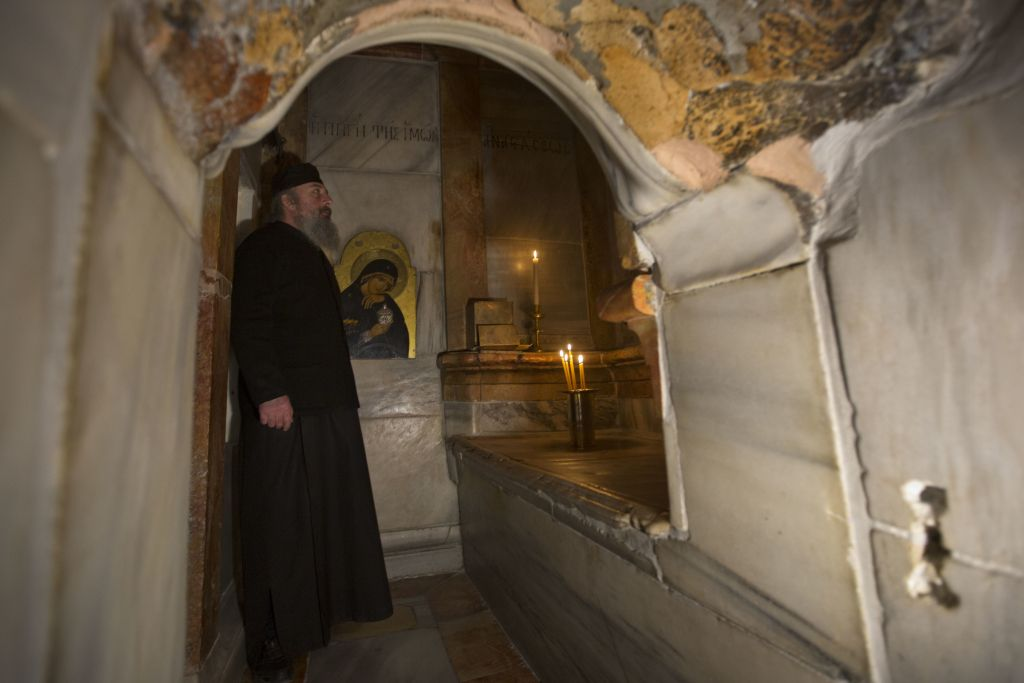 A Greek priest stands inside the renovated Edicule in the Church of the Holy Sepulchre, traditionally believed to be the site of the crucifixion of Jesus, in Jerusalem's Old City, March 20, 2017. A Greek restoration team has completed a historic renovation of the Edicule, the shrine that tradition says houses the cave where Jesus was buried and resurrected. (AP Photo/Sebastian Scheiner)
