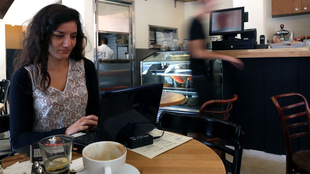 A woman works remotely on her laptop at a coffee shop in downtown Jerusalem. (Nati Shohat/Flash90)