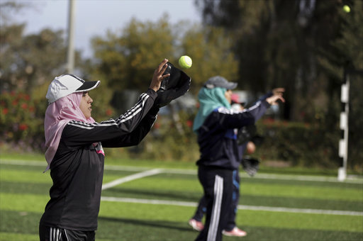 In this Sunday, March 19, 2017 photo, Palestinian women practice with tennis balls while training for an all women's baseball game, on a soccer field in Khan Younis, southern Gaza Strip. (AP Photo/Khalil Hamra)