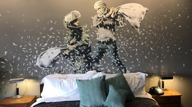 An Israeli solider and Palestinian man have a pillow fight in one of the Banksy artworks on the walls of the hotel. [Picture: Channel 4] (March 2017)