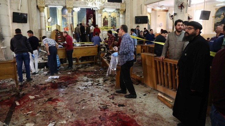 A general view shows people looking at the aftermath following a bomb blast which struck worshippers gathering to celebrate Palm Sunday at the Mar Girgis Coptic Church in the Nile Delta City of Tanta, north of Cairo, on April 9, 2017. (AFP Photo/Stringer)