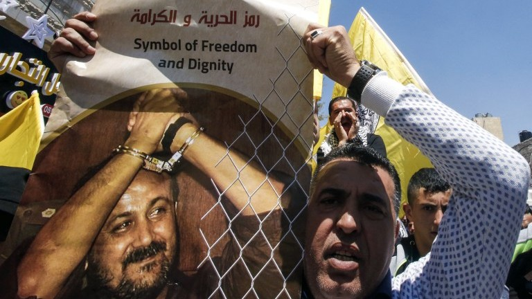 A man holds a photo of convicted Palestinian terrorist Marwan Barghouti calling for his release during a rally supporting those detained in Israeli jails after hundreds of prisoners launched a hunger strike, in the West Bank town of Hebron on April 17, 2017. (AFP Photo/Hazem Bader)