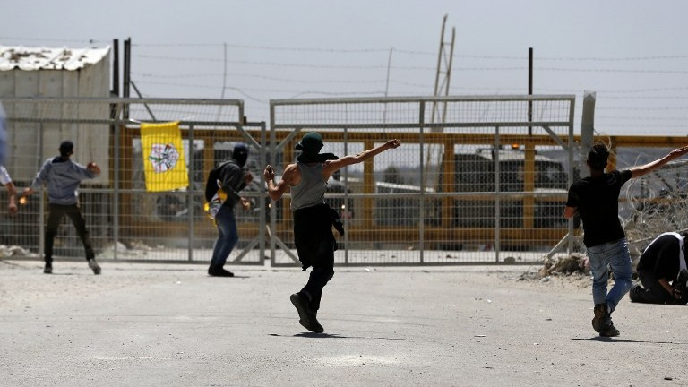 Palestinian protesters hurl stones towards Israeli security forces during clashes in front of Ofer Prison in the West Bank village of Betunia on April 20, 2017. (AFP Photo/Abbas Momani)