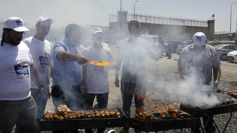 Israeli right-wing activists barbecue outside Ofer Prison in the West Bank village of Betunia on April 20, 2017. (AFP Photo/Menahem Kahana)