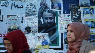 Palestinian women walk past a wall bearing posters, including a portrait of prominent prisoner Marwan Barghouti, during a rally in the West Bank city of Ramallah in support of him and other prisoners on hunger strike in Israeli jails on April 24, 2017. (AFP/Abbas Momani)