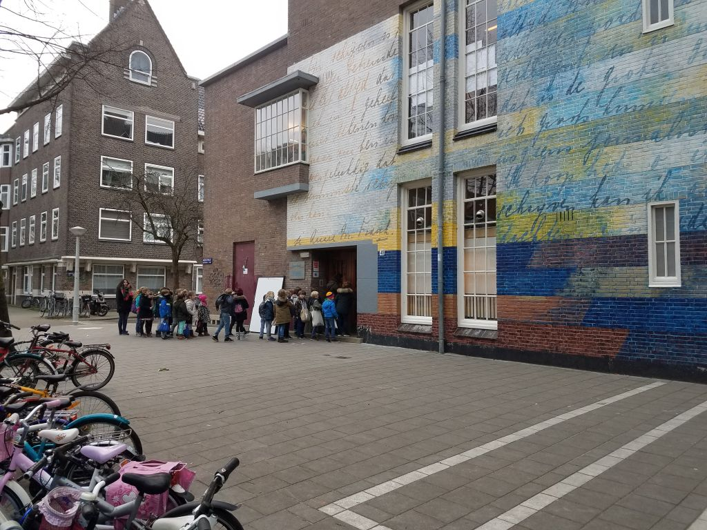 The Anne Frank Montessori School in Amsterdam's River Quarter, where the diarist attended school beginning in 1934. Text from Frank's diary set against vibrant colors now adorns the otherwise unchanged building, January 2017. (Matt Lebovic/The Times of Israel)