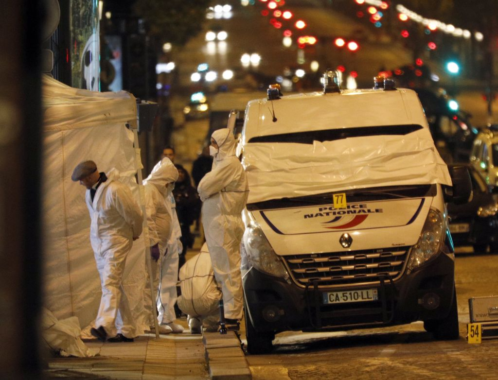 Forensic experts investigate the crime scene after a fatal shooting in which a police officer was killed along with an attacker on the Champs Elysees avenue in Paris, France, Friday, April 21, 2017.(AP Photo/Kamil Zihnioglu)