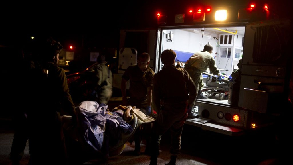 In this Thursday, April 6, 2017 photo taken in the Golan Heights, Israeli military medics assist wounded Syrians. (AP Photo/Dusan Vranic)