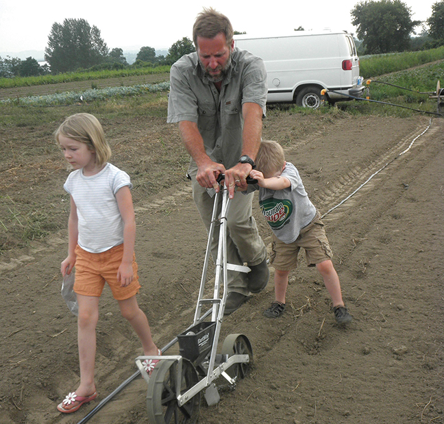 Ken Fruehstorfer introduces his children, Alix and Xavier, to the chores needed to make their organic farm a success.