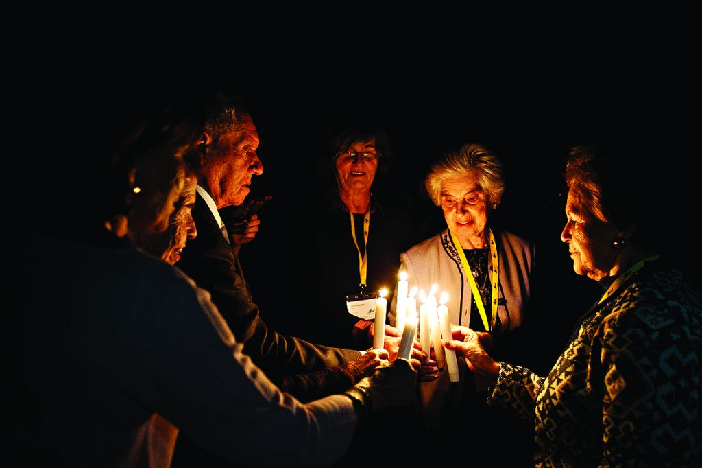 Survivors including Tana Fox, Eve Kugler, Arek Hersh, Vesna Domany Hardy, Renee Salt and Mala Tribich take part in havdallah.