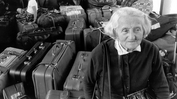 An elderly woman guards luggage in an Austria train station in 1989. (Courtesy 'Stateless')